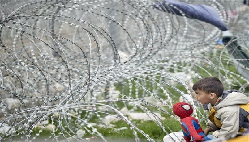 A boy plays with a Spiderman doll next to the razor wire around the fence between Greece and Macedonia at the northern Greek border station of Idomeni, Monday, March 7, 2016.  Greek police officials say Macedonian authorities have imposed further restrictions on refugees trying to cross the border, saying only those from cities they consider to be at war can enter as up to 14,000 people are trapped in Idomeni, while another 6,000-7,000 are being housed in refugee camps around the region.(AP Photo/Vadim Ghirda)